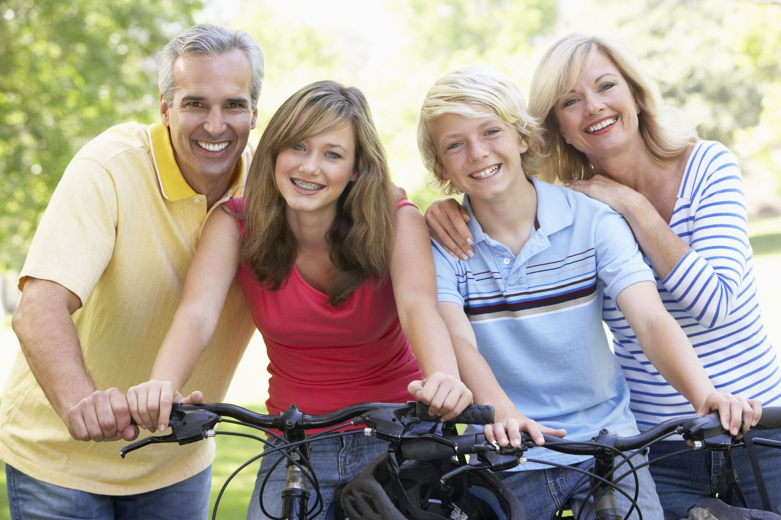 Family smiling and riding bicycles